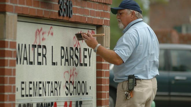 Tom Dixon with the New Hanover County Schools Maintenance Department uses lacquer thinner and a paint brush to remove spray paint graffiti from the marquee outside Walter L. Parsley Elementary School Wednesday Aug. 23, 2006.