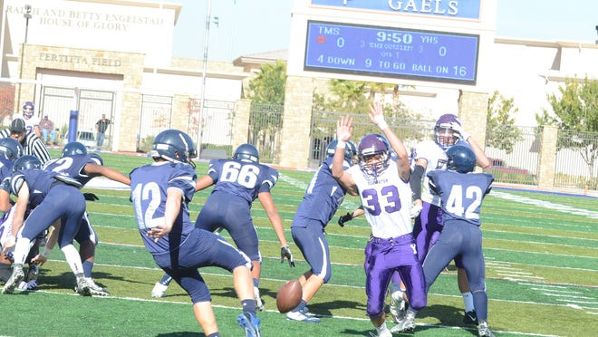 Yerington's Harrison Cisneros leaps to block this punt by The Meadows' Jacob Gleason, which went out of the end zone for a safety to open the scoring in Yerington's 45-14 NIAA Division III state championship game victory Saturday in Las Vegas.