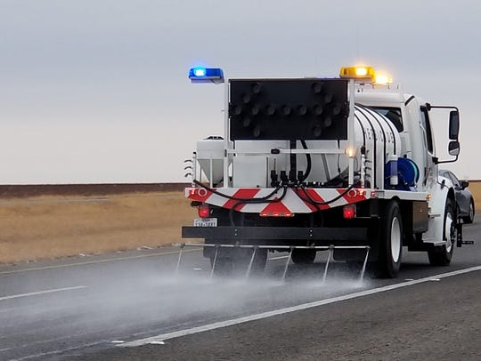 A road crew treats U.S. Highway 277 in Haskell County