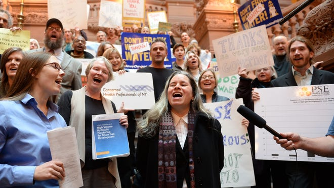 """Singer Natalie Merchant leads a group of anti-fracking activists in a rendition of Pete Seeger's """"This Land is Our Land"""" on Dec. 18 in Albany to thank Gov. Andrew Cuomo and state officials for banning fracking."""