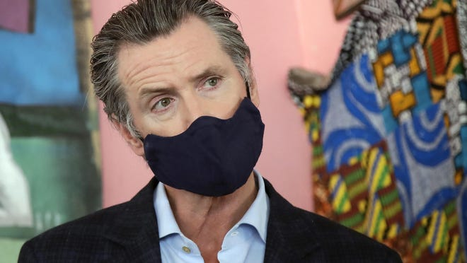FILE - In this June 9, 2020, file photo, California Gov. Gavin Newsom wears a protective mask on his face while speaking to reporters at Miss Ollie's restaurant during the coronavirus outbreak in Oakland, Calif. According to a new poll, Americans overwhelmingly are in favor of requiring people to wear masks around other people outside their homes, reflecting fresh alarm over spiking infection rates. The poll also shows increasing disapproval of the federal government's response to the pandemic. California is among the states seeing the greatest surge in cases now.