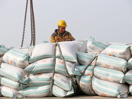 A worker moves bags of soybean meal at a port in Nantong, China on March 22, 2018.