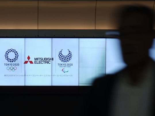 In this Sept. 30, 2017 photo, a man walks by an advertisement screen showing Mitsubishi Electric, one of Tokyo 2020 Olympics sponsors, at Tokyo Station in Tokyo. Tokyo is a well-known global capital, and the Summer Games usually generate more excitement and money. Organizers already have raised 300 billion yen ($2.7 billion), twice any previous Olympics. International Olympic Committee Vice President John Coates describes it as a remarkable achievement. (AP Photo/Eugene Hoshiko)