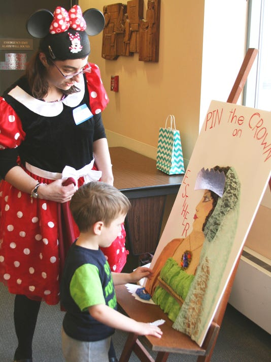 Rabbi Brody as Minnie Mouse assisting a child with Purim game
