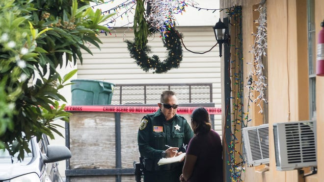 A PBSO deputy talks to a resident who lives near the spot where a man was killed in Lake Worth Beach Wednesday morning, December 18, 2019.