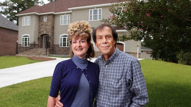 Bill and Dorrie Benners stand in front of the their rebuilt Turtle Bay residence. The Benners' home and  possessions were destroyed by storm damage and a catastrophic fire during Hurricane Florence in 2018. The Benners moved back into their house in June 2020.