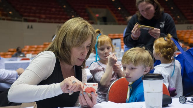 Screeners use apps to calculate body mass during the Healthy Tennessee health fair at the Oman Arena on Saturday.