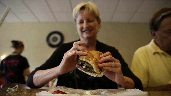 Sue Diehl takes a look at her sandwich before her first bite at Mihm's Charcoal Grill on Wednesday. The Menasha diner is a go-to favorite for many.