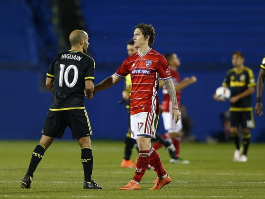 Columbus Crew's Federico Tiguan (10) and FC Dallas' Zach Loyd (17) shake hands after they played in an MLS soccer match in Frisco, Texas, Saturday, April 2, 2016. (AP Photo/Ralph Lauer)