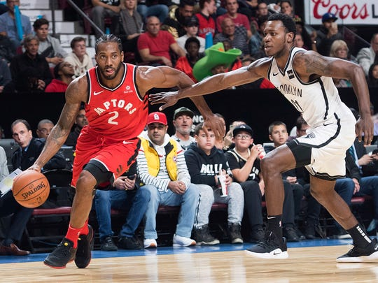 Toronto Raptors' Kawhi Leonard (2) drives to the basket as Brooklyn Nets' Treveon Graham defends during the first half of an NBA basketball preseason game Wednesday, Oct, 10, 2018, in Montreal. (Graham Hughes/The Canadian Press via AP)