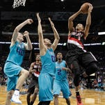 Portland Trail Blazers' C.J. McCollum (3) shoots over Charlotte Hornets' Spencer Hawes (00) and Cody Zeller (40) during the first half of an NBA basketball game in Charlotte, N.C., Sunday, Nov. 15, 2015.