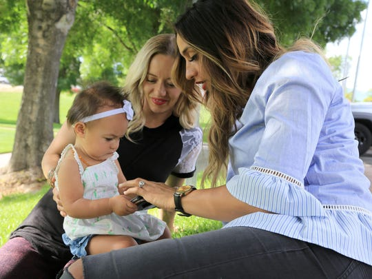 "In honor of her role as an egg donor, Tia Stokes, right, has taken on the role of ""auntie"" for baby Giselle, left, who was conceived via in vitro fertilization and then transferred to her mother, Chelsea, center."
