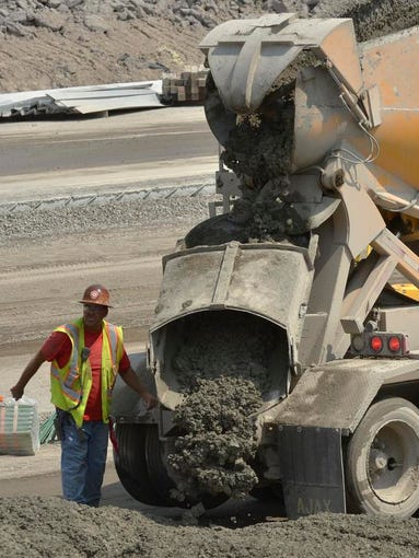 A constant stream of trucks dumps concrete that will become finished road surface, in a matter of minutes.