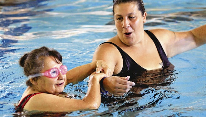 Angel Trujillo leads athlete Sammy Trujillo in an assisted 25-meter swim race Aug. 17, 2013, during a Special Olympics competition at the Farmington Aquatic Center.