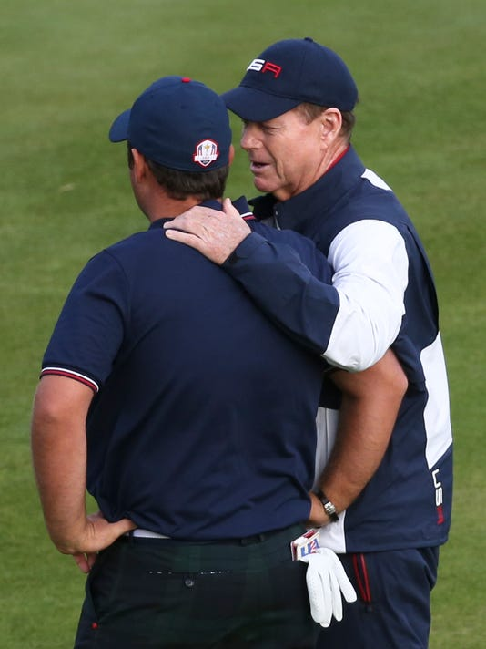 US team captain Tom Watson consoles Patrick Reed after losing the 18th hole and halving the foursomes match on the second day of the Ryder Cup golf tournament, at Gleneagles, Scotland, Saturday, Sept. 27, 2014. (AP Photo/Scott Heppell)