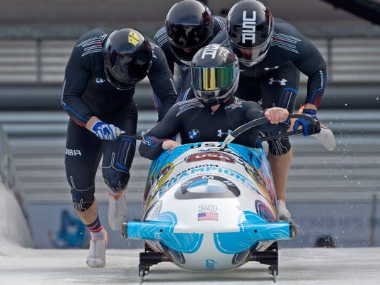 FILE - In this March 7, 2015, file photo, driver Codie Bascue, front, and his United States team, push off at the start during the first run of the four-man bobsled competition at the Bobsled and Skeleton World Championships in Winterberg, Germany. Drivers Justin Olsen, Nick Cunningham, Codie Bascue will lead the U.S. Olympic bobsled team. (AP Photo/Jens Meyer, File)