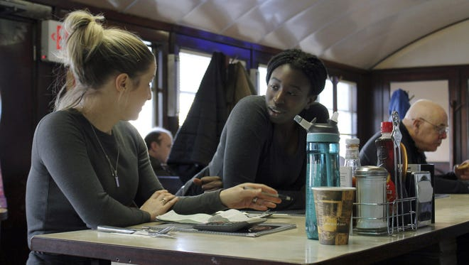 In this Jan. 25, 2019, waitress Kelcie Tipping, left, speaks with fellow waitress Mariam Touray, right, at the Modern Diner in Pawtucket, R.I.