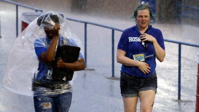 Drenched employees leave as Def Leppard performs at the American Family Insurance Amphitheater July 4.