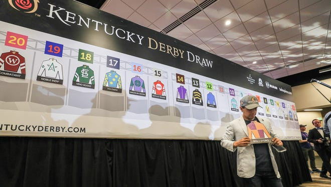 Victor Espinoza, who is riding Bold D'Oro, pulls the placard down and holds it after the draw for post positions for the 144th Running of the Kentucky Derby on Tuesday at Churchill Downs.May 1, 2018