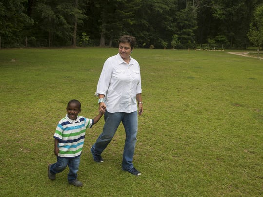 Lisa Pontoriero and her adopted son Ryder hold hands