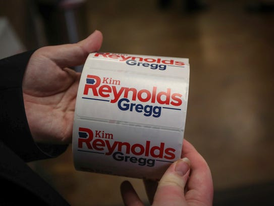 A volunteer hands out stickers for Gov. Kim Reynolds