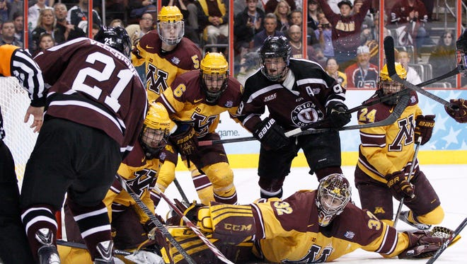 Minnesota goalie Adam Wilcox, bottom right, reaches for the puck as Union's Mike Vecchione, left, shoots into a crowd of players Saturday night in Philadelphia.