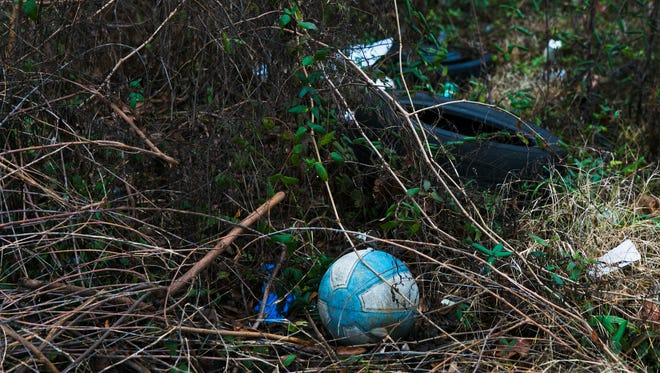 A discarded basketball, a used tire and other debris litter a spot behind a business in Orange Mound on Jan. 11, 2017.