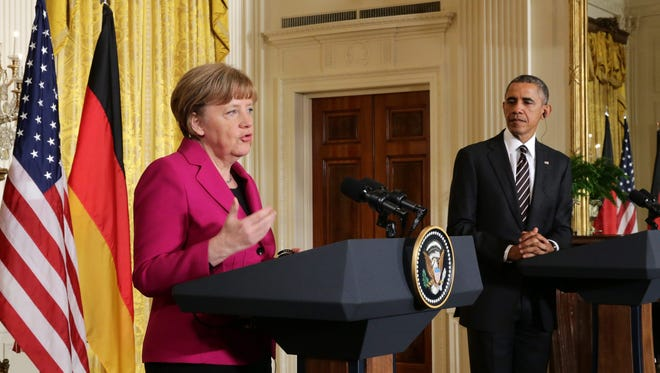 President Obama listens to Chancellor of Germany Angela Merkel during a joint news conference at the East Room of the White House Monday. Obama and Merkel met in Washington to discuss a wide variety of issues including Ukraine, Russia, Iran, Afghanistan, counter-terrorism, international trade and the forthcoming G-7 Summit in June 2015.  EPA/MICHAEL KAPPELER ORG XMIT: FAX202