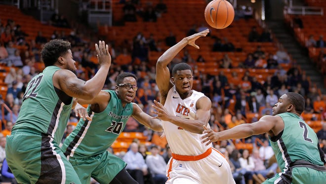 UTEP's Tevin Caldwell passes to a teammate after drawing a trio of UNT defenders Sunday at the Don Haskins Center.