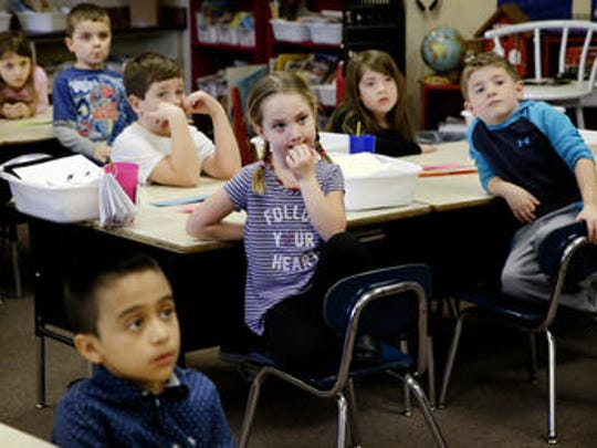The first-grade class of Jackie Siwik listens close as Danesa Stolz, chief naturalist with the Fishers Parks and Recreation Department, talks with them about maple trees at Brooks School Elementary on Feb. 23, 2016.
