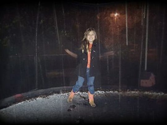Madisyn Na'Jera plays in the snow outside her home
