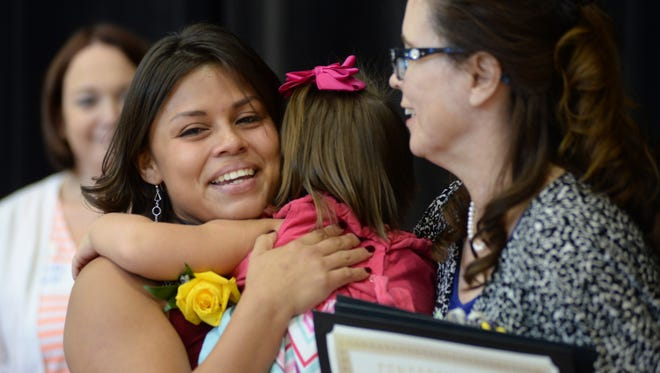 photos by Rachael Le Goubin/The Republic At the Family Reunification Day celebration in Phoenix June 13, Jessica Rodriguez hugs daughter Lola after recount- ing the hardships in her life that resulted in her children being placed into foster care. They were reunited in 2014. Jessica Rodriguez hugs her daughter Lola after recounting the hardships in her life that resulted in her two children being placed into foster care during the second annual Reunification Day Celebration at Rest Baptist Church in Phoenix on Saturday, June 13, 2015. On Reunification Day, Maricopa county honors families where parents have been deemed stable enough to be reunited with their children from the foster care system.