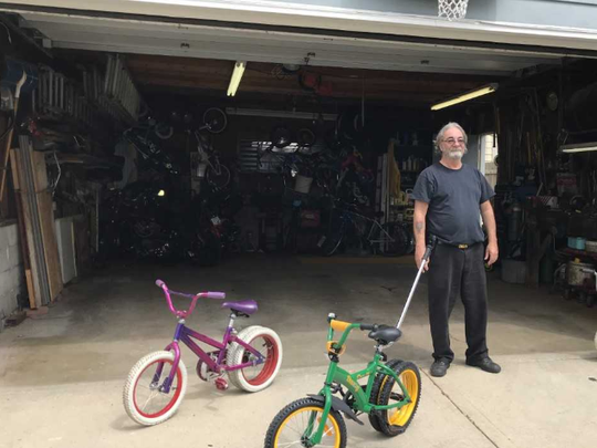 From a garage in West Allis, a new kind of more stable bicycle has arisen. Inventor Jeffrey Gaudynski stands at the garage door with the first model he built (purple one in back) and the  model that is fresh from the manufacturer that is now for sale.