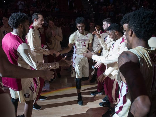 FILE - In this Dec. 18, 2017, file photo, Florida State junior guard Terance Mann (14) is introduced before an NCAA basketball game against Charleston Southern in Tallahassee, Fla.  Mann is one of the few Division I players who learned most of the game from his mom. (AP Photo/Mark Wallheiser, File)