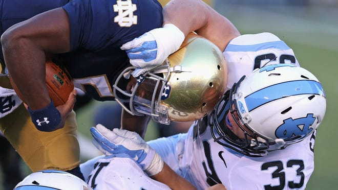 SOUTH BEND, IN - OCTOBER 11: Nathan Staub #33 of the North Carolina Tar Heels brings down Everett Golson #5 of the Notre Dame Fighting Irish at Notre Dame Stadium on October 11, 2014 in South Bend, Indiana. Notre Dame defeated North Carolina 50-43. (Photo by Jonathan Daniel/Getty Images)