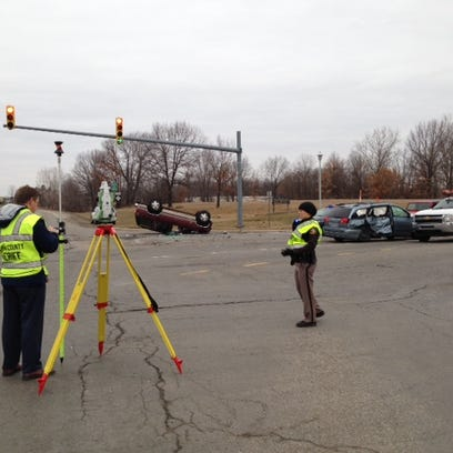 Investigators work at the scene of a crash at Helmer and Dickman roads Thursday morning that left two people, including a child, seriously injured.