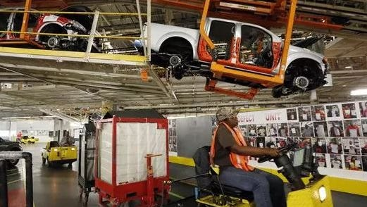 In this April 6, 2016 photo, vehicles are suspended above other installation stations as they are moved along the assembly line at the Nissan Canton Vehicle Assembly Plant in Canton, Miss.