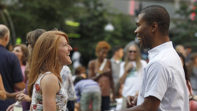 Jill Grear of Monfort Heights and Malik Spencer of Downtown dance during Salsa on the Square at Fountain Square on Thursday July 17, 2014.