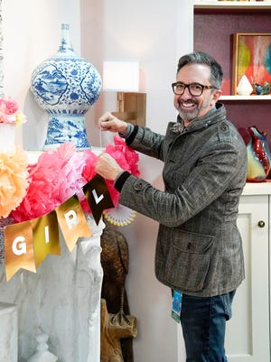 Peter Gurski decorates the fireplace mantel on the set of a TV show.