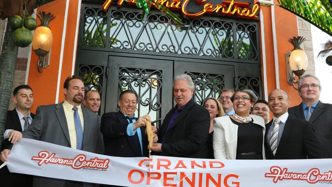(l) Jeremy Merrin, owner of Havana Central and Edison Mayor, Tom Lankey, cut the ribbon during the grand opening ceremony of Havana Central located at the Menlo Park Mall, Edison, NJ, November 4, 2015.  Mary Iuvone/For the Courier News