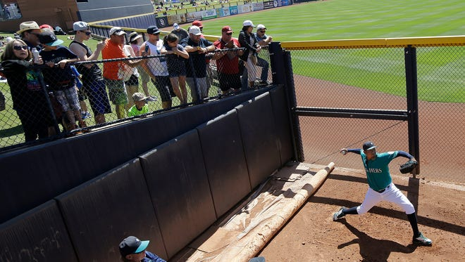 Fans watch as Seattle Mariners starting pitcher Felix Hernandez throws in the bullpen before a spring training baseball game between the Mariners and the San Diego Padres in Peoria, Ariz., Wednesday, March 30, 2016.