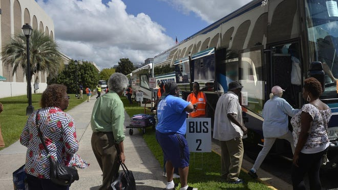 A line of people board a charter bus at Savannah's Civic Center to an inland shelter as residents evacuate from Hurricane Dorian, Tuesday, Sept. 3, 2019.