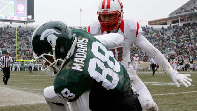 Michigan State's Monty Madaris (88) is pushed out of bounds by Rutgers' Anthony Cioffi after a 24-yard reception Saturday, Nov. 22, 2014, in East Lansing.