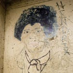 Art of Jimi Hendrix and the names of songs of the time cover the interior of a cell at the former York County Prison in October 2007. The prison closed in 1979.