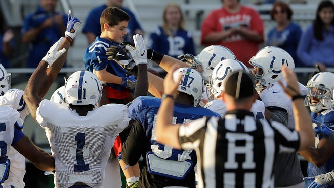 Michael Dieter, 10, top, celebrates with the Indianapolis Colts after scoring a touchdown during practice at the NFL team's football training camp Saturday, Aug. 5, 2017, in Indianapolis. Dieter has had eight heart surgeries, including full heart transplant less than a year ago.