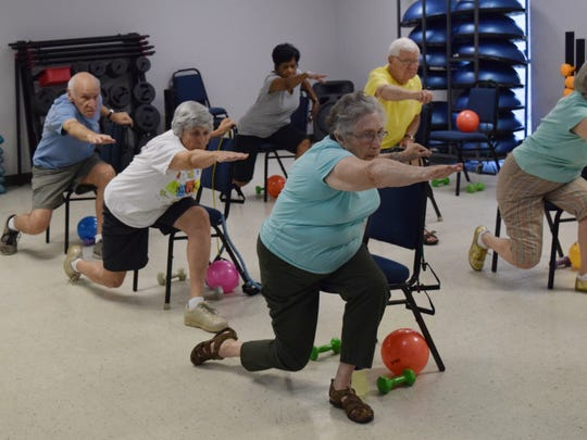 Rabbi Arnold Task (far left), his wife Judy Task and Sissy Dayan perform stretching exercises in the Chair Aerobics class at the Turner Street YWCA.