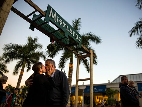 Peter Moscatelli kisses his wife, Pamela, under a mistletoe archway during the annual Christmas on Third celebration in downtown Naples on Monday, Nov. 21, 2016. The event featured tree lighting, ice sculptures, music and fake snow.