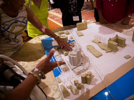 Residents discuss the development over a 3-D rendering of the property during an open house Wednesday, May 17, 2017, at the Ritz Carlton beach resort in North Naples. Vanderbilt Holdings LLC, an affiliate of Stock Development, wants to develop a project called One Naples that would include Stock Development's first high-rise, an 18-story condo building over three levels of parking.