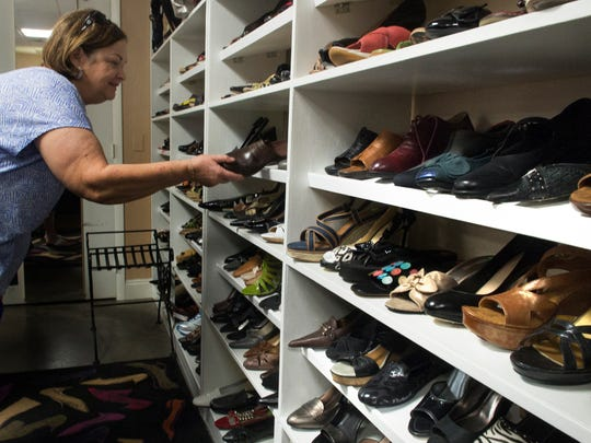 Jo Carlson shops for shoes, Friday (8/8/14) at the Cecilia's Elite Repeat consignment boutique on U.S. 41 in Fort Myers.