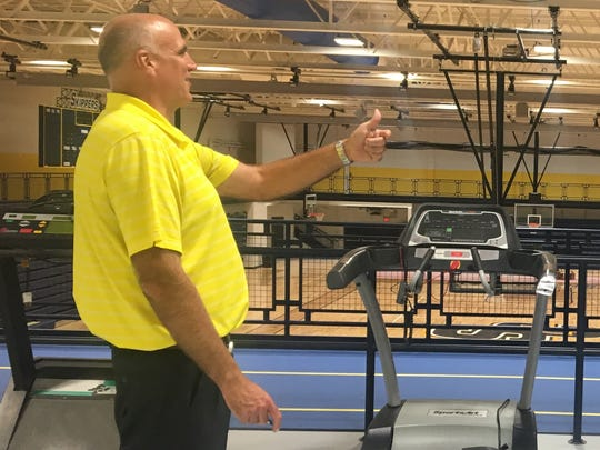 Athletic Director Dale Vos stands above the court in